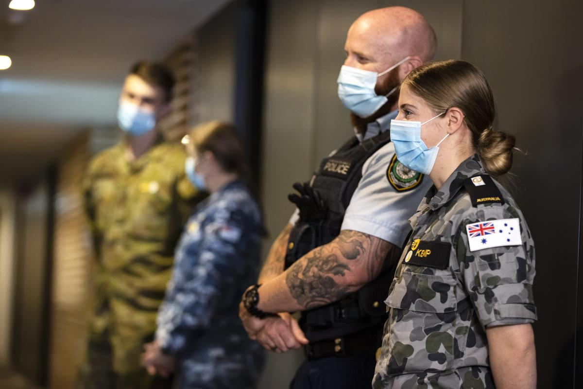 NSW Police Senior Constable Peter Heginbotham, front left, and Midshipman Bridie Kemp on hotel quarantine duties during Operation COVID-19 Assist. Photo: Corporal Dustin Anderson