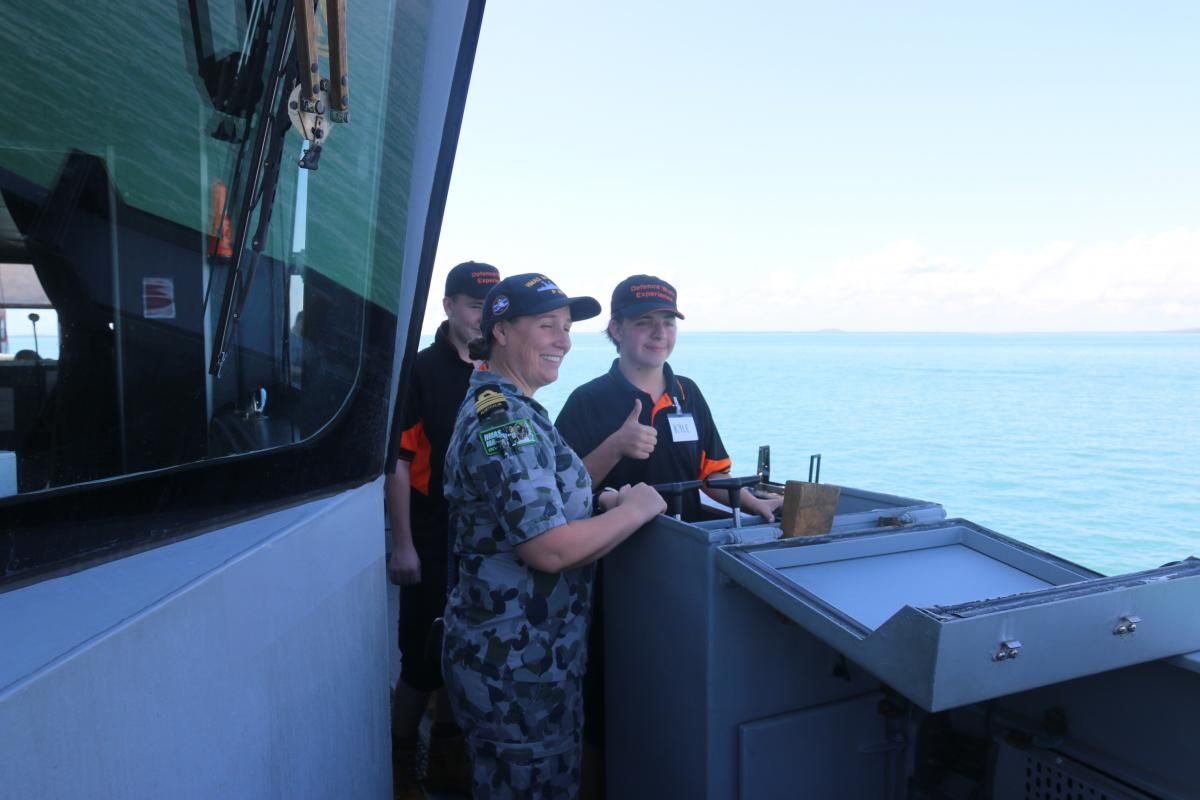 Commanding Officer HMAS Maitland Lieutenant Commander Julia Griffin shows Kyle Firgula-White and Alex Ryan how to drive the ship.