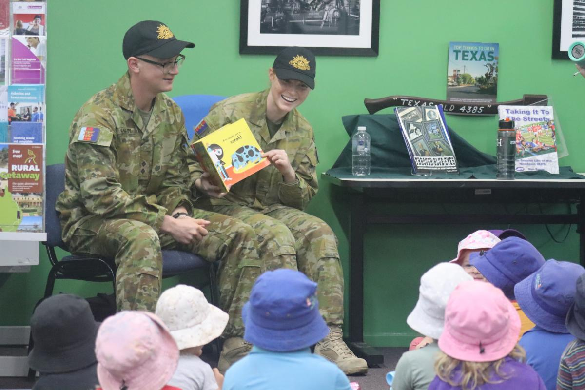 Lieutenant Thomas McAllister and Private Nikita Booth read a story to some children at the library in Texas, Queensland.