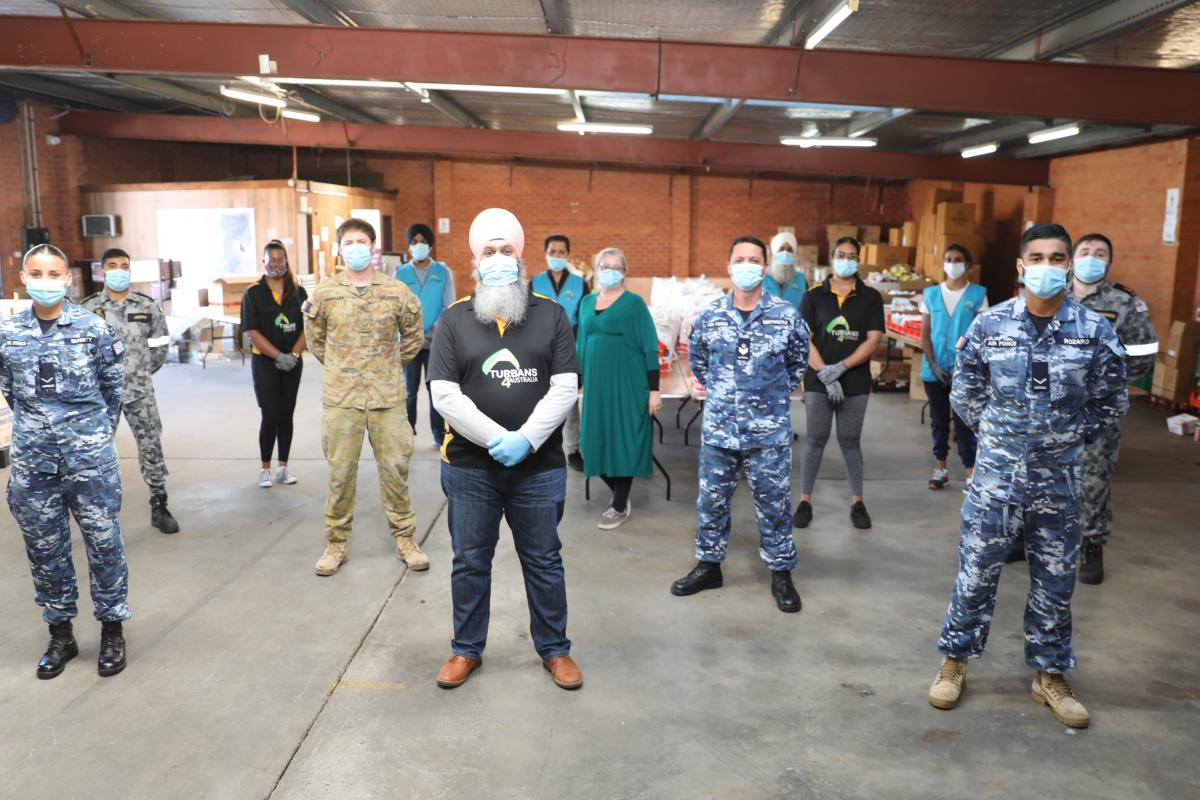Turbans 4 Australia President Amar Singh with ADF members at the charity's warehouse in Clyde, NSW.