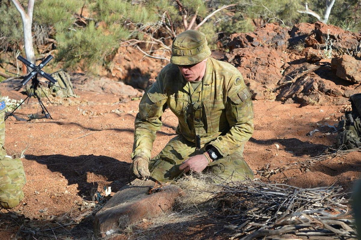 Corporal Andrew Ball demonstrates lighting a fire with a fero rod on Exercise Emu Walk.